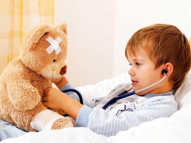 bambino a letto gioca facendo finta di visitare il suo orsacchiotto malato