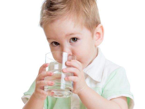 bambino beve un bicchiere d'acqua