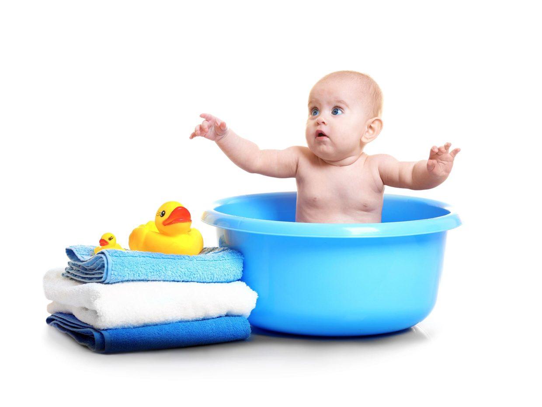 bambino fa il bagno su una bacinella blu con a fianco pila di asciugamani