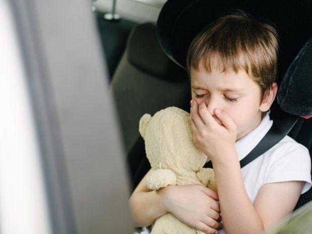bambino in macchina con mano davanti alla bocca abbracciato al suo orso di peluche