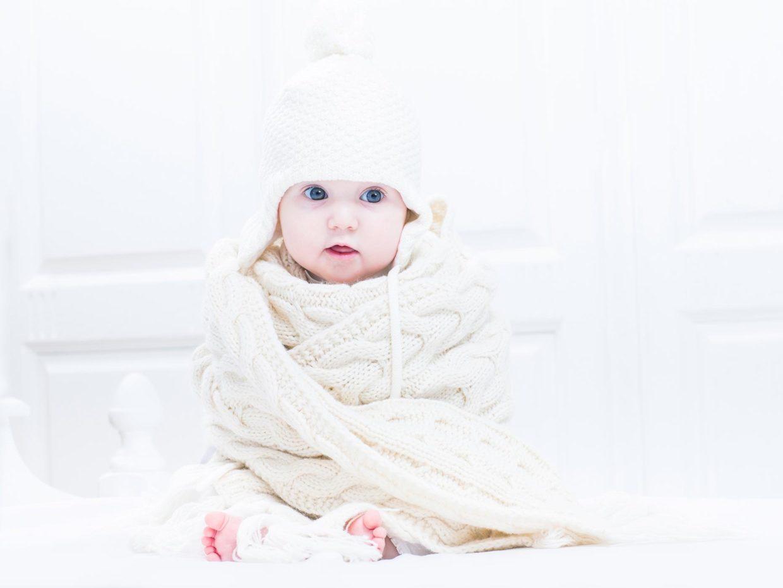 bambino avvolto in una coperta bianca con cappello di lana in testa