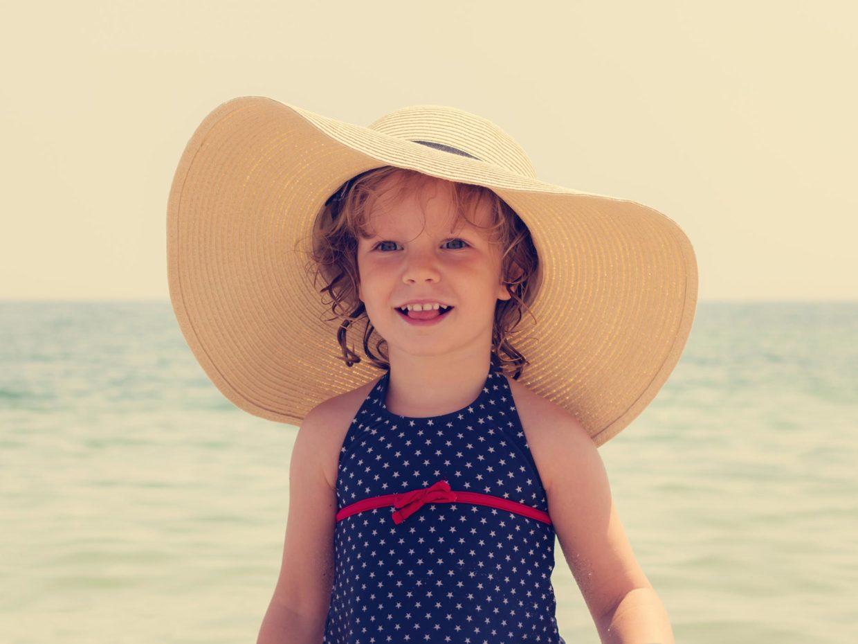 bambina con cappello di paglia a banda larga in spiaggia