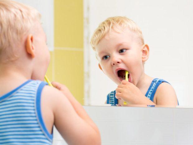 bambino si guarda allo specchio mentre si pulisce i denti