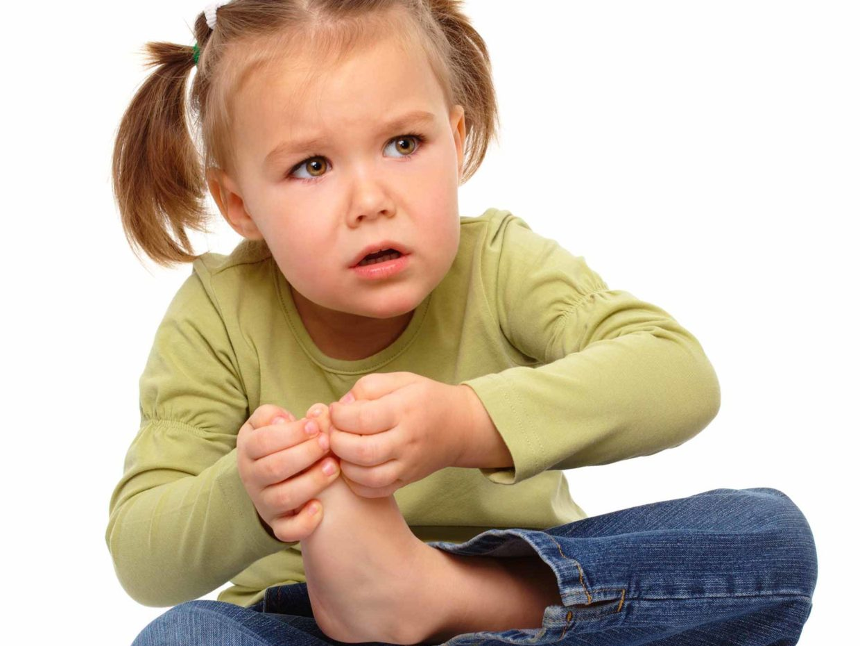 bambina si tocca il piede dolorante