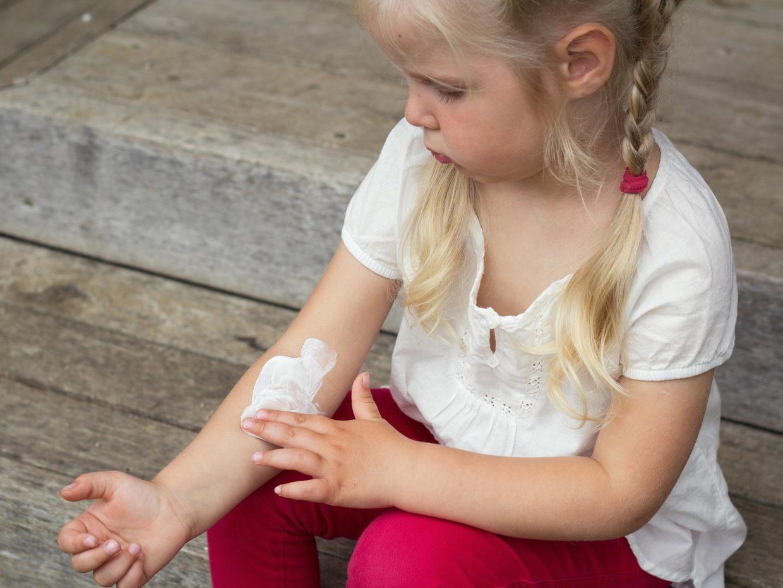 bambina bionda spalma crema sul suo braccio