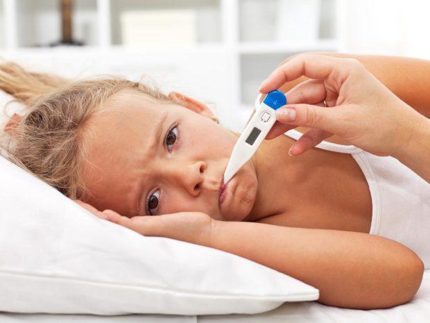 bambina triste con termometro in bocca