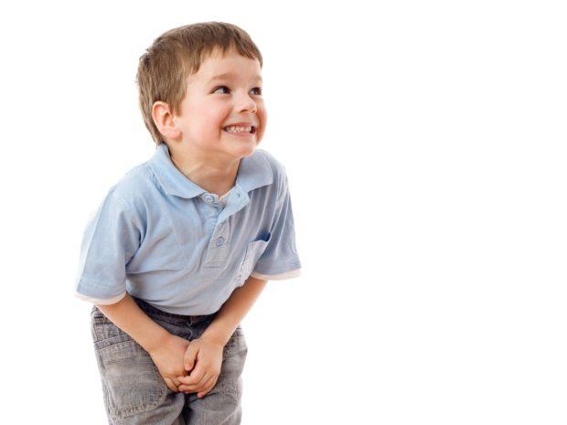 bambino sorridente su sfondo bianco piegato in avanti