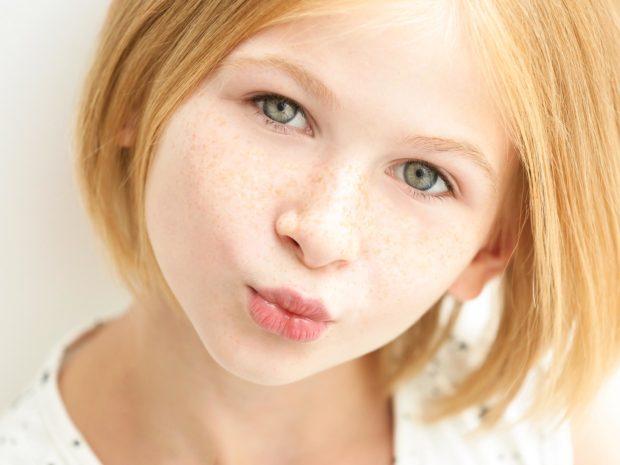 volto di bambina con lentiggini sul naso e sulle guance