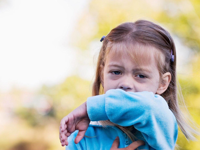 bambina si copre la bocca con il braccio