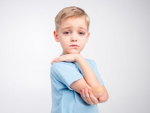 ragazzino triste si tocca il gomito dolorante