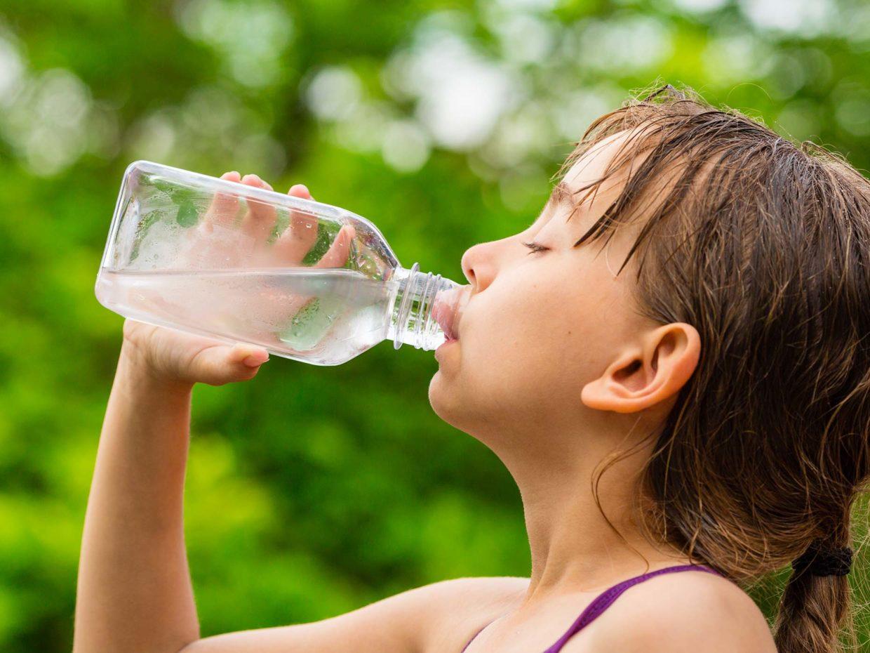 bambina sudata beve acqua dalla bottiglia