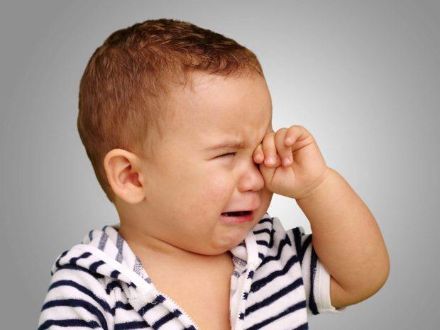 bambino piange disperato strofinandosi occhio