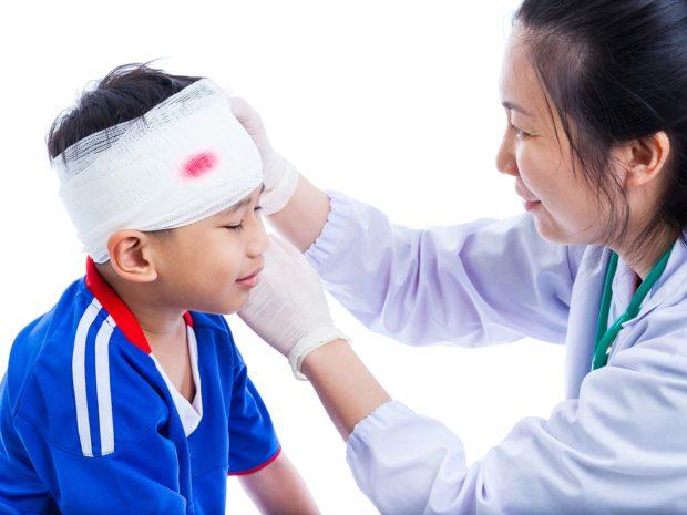 pediatra fascia la testa ferita del bambino con garze sterili