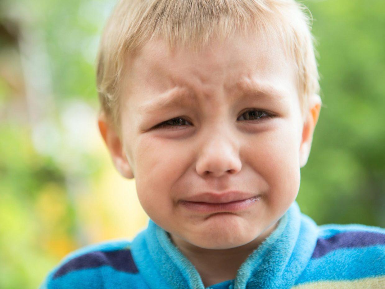 primo piano di ragazzino biondo con volto sofferente