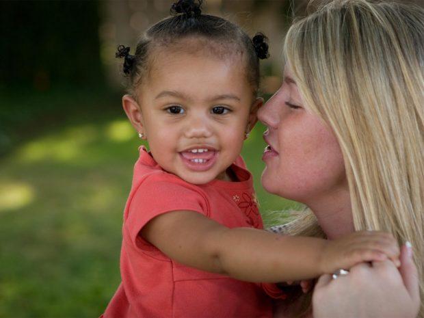 bambina di colore in braccio alla madre adottiva