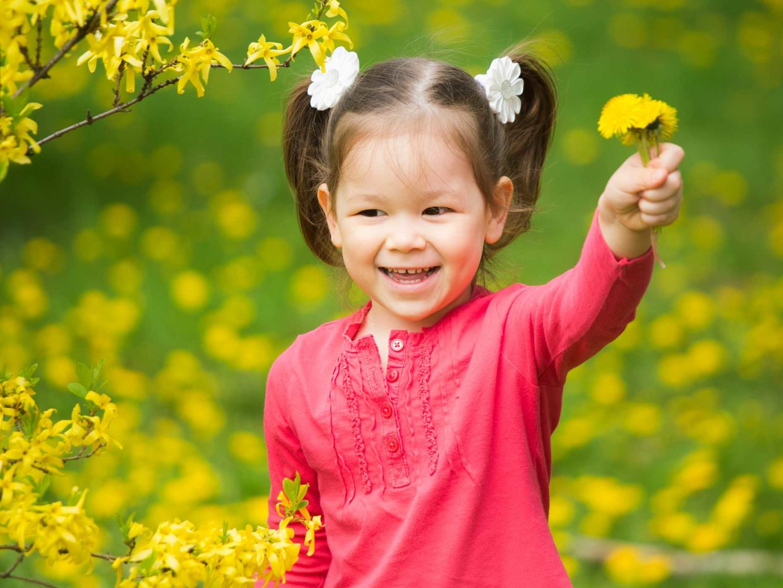 bambina asiatica tiene in mano fiori gialli in un giardino