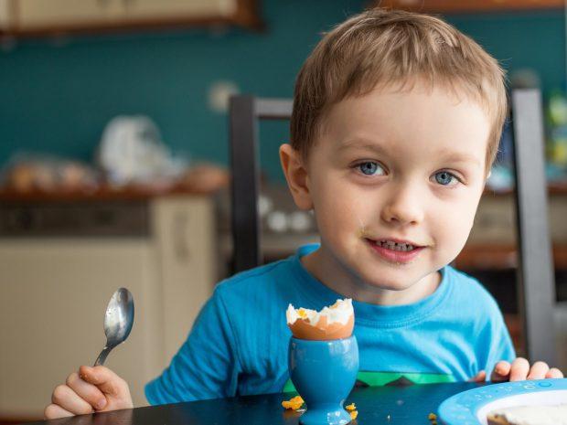 bambino sorridente mangia uovo alla coque