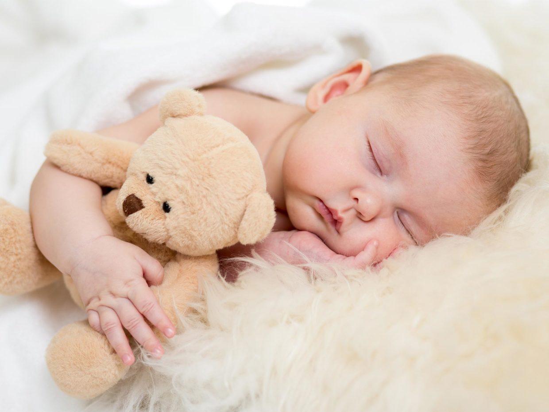 neonato dorme sereno abbracciato al suo orsacchiotto di peluche