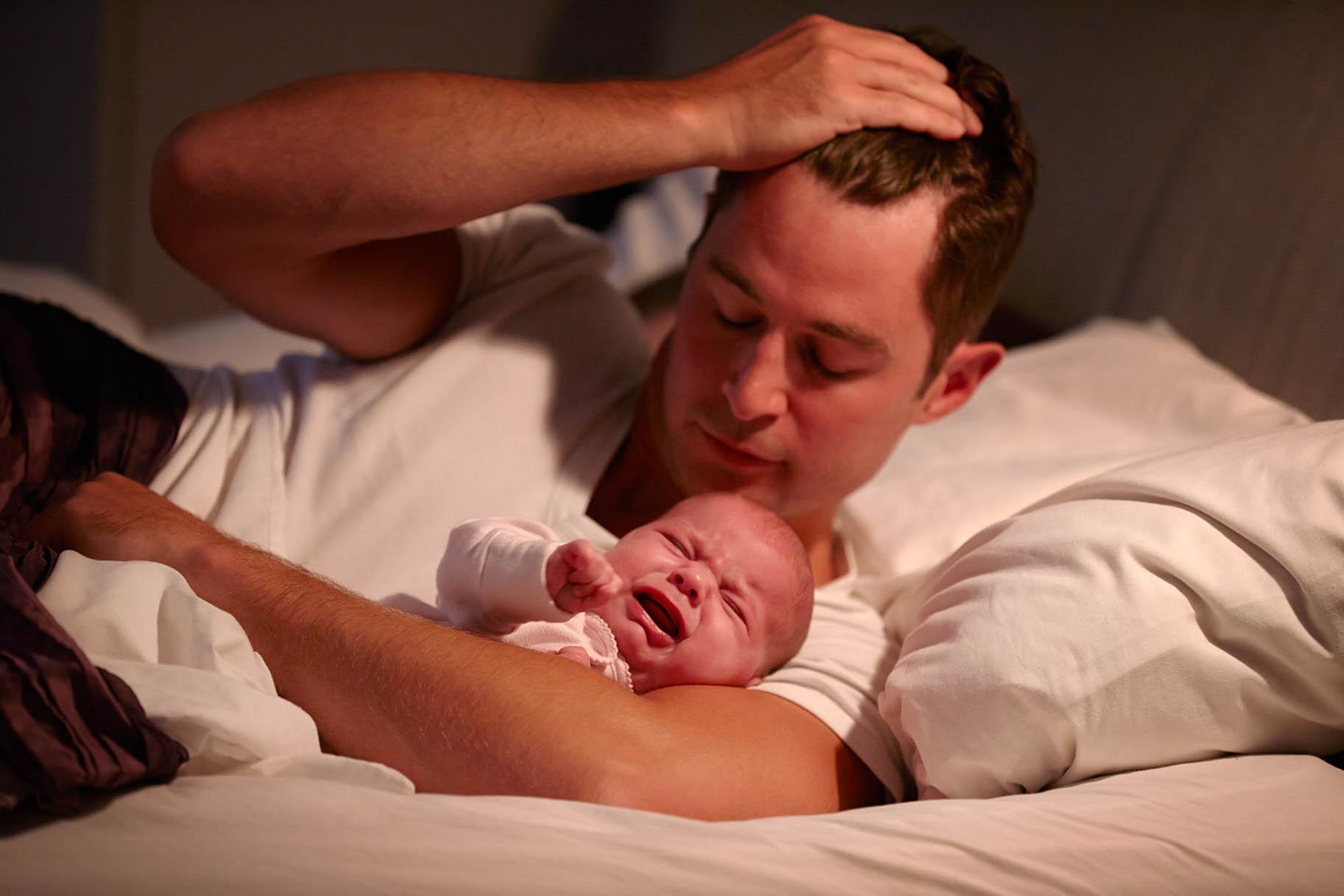 papà con mano nei capelli abbraccia nel letto il figlio che piange
