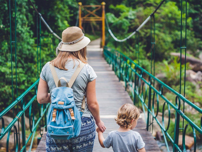 mamma e figlio passeggiano su un ponte in mezzo alla natura