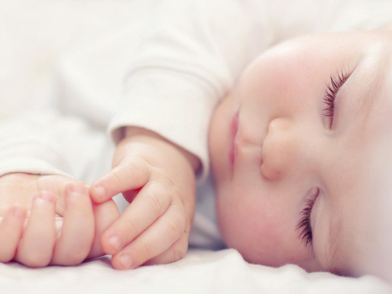 primo piano su un neonato che dorme sul fianco