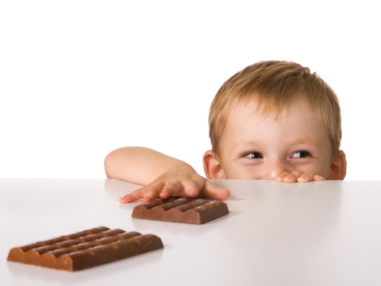 bambino prova a prendere le barrette di cioccolato da un tavolo