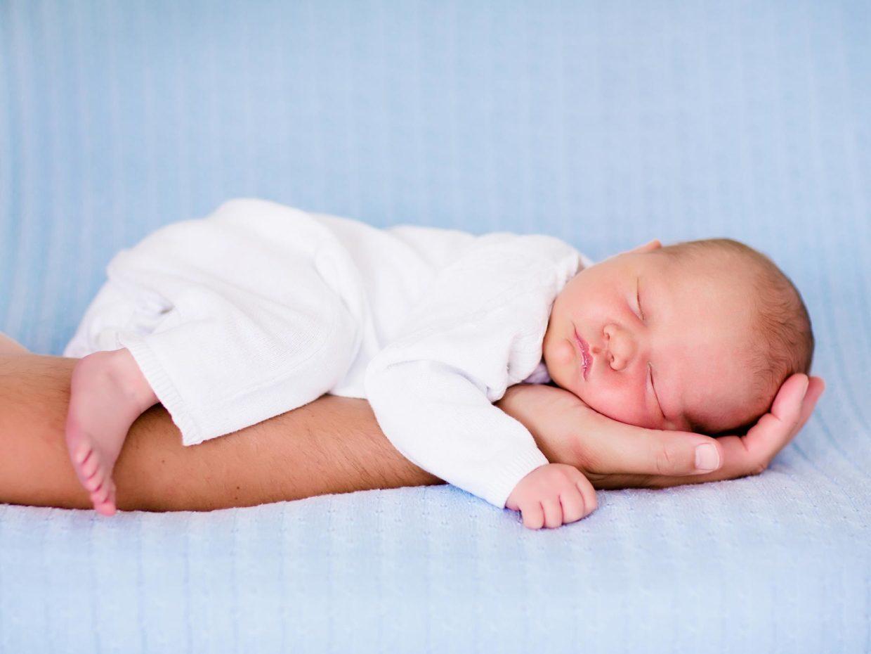 neonato dorme sul braccio di un adulto