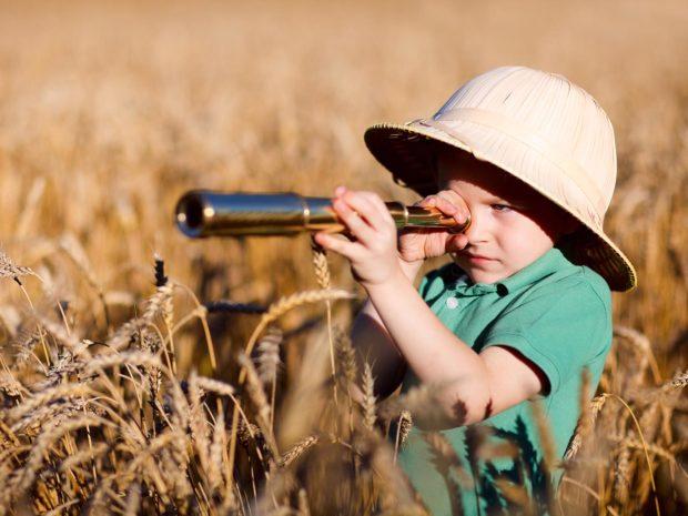 bambino con cappello da esploratore in mezzo ad un campo di spighe di grano guarda attraverso un binocolo