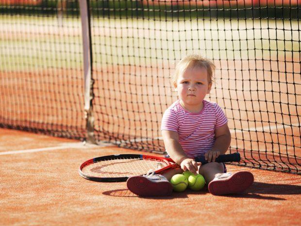 bambino piccolo seduto su un campo da tennis con in mano racchetta e palline