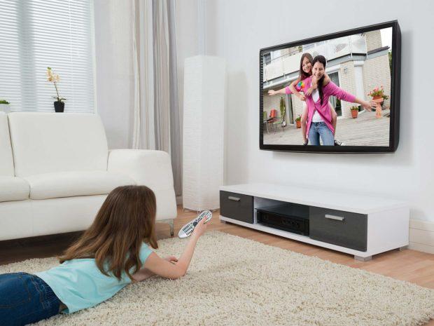 bambina distesa per terra guarda la televisione