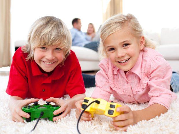 due bambini biondi sorridenti con in mano i joystick