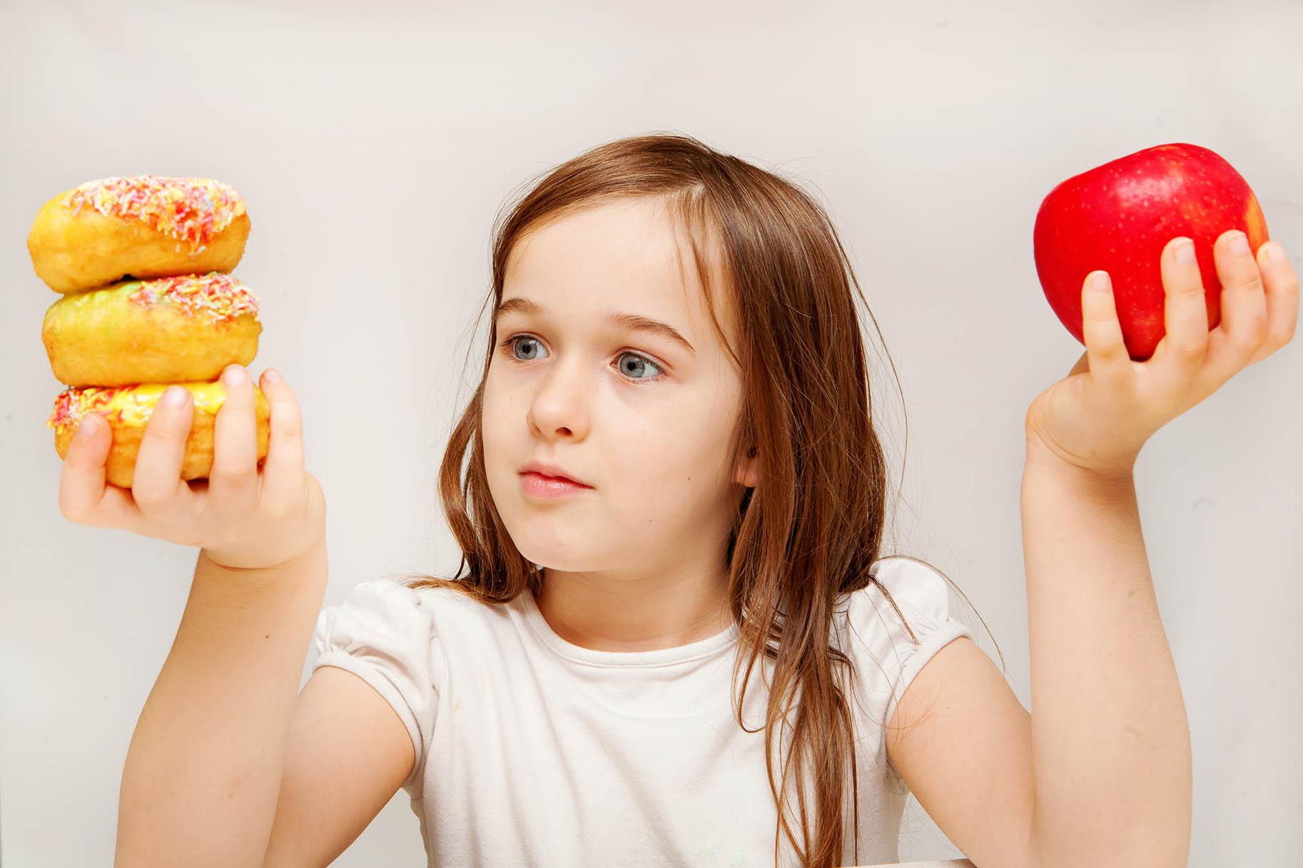 bambina con in mano da un lato una mela dall'altro delle ciambelle