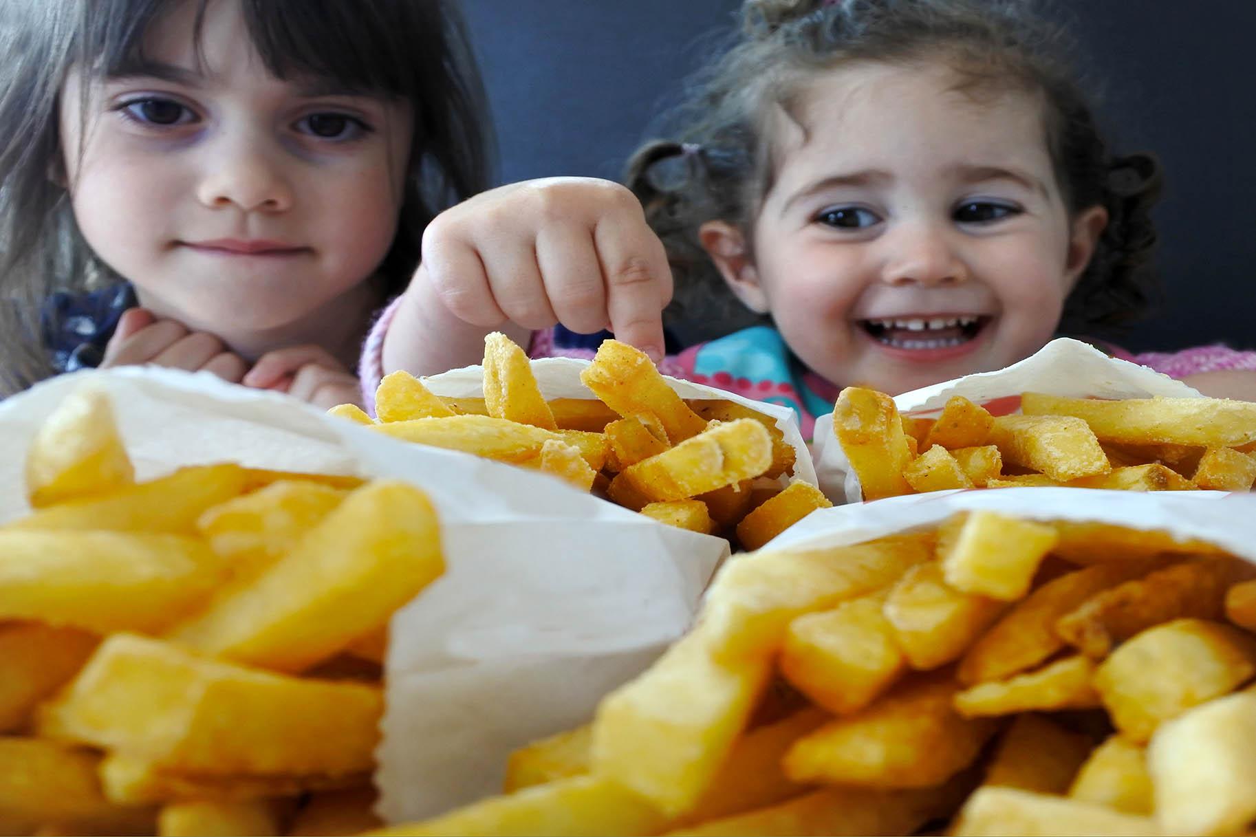 piccole bambini mangiano le patatine fritte