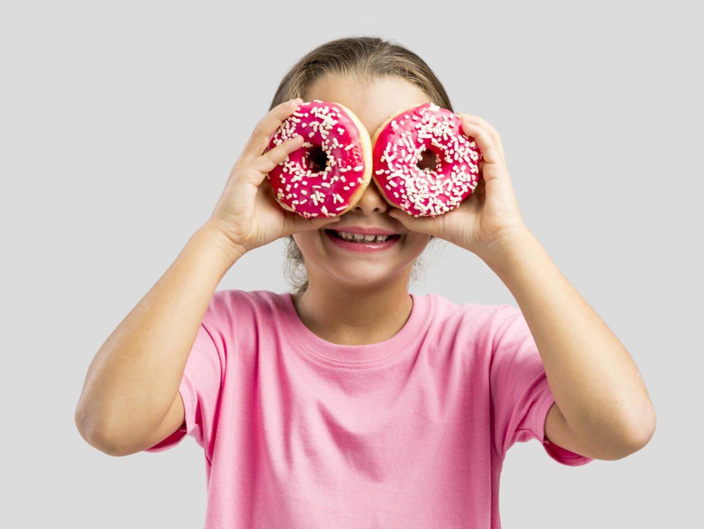 bambina gioca con le ciambelle usandole come occhiali