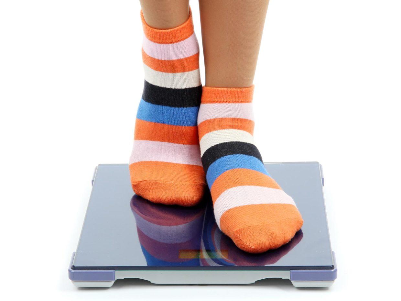 bambina sopra la bilancia con calze a righe colorate