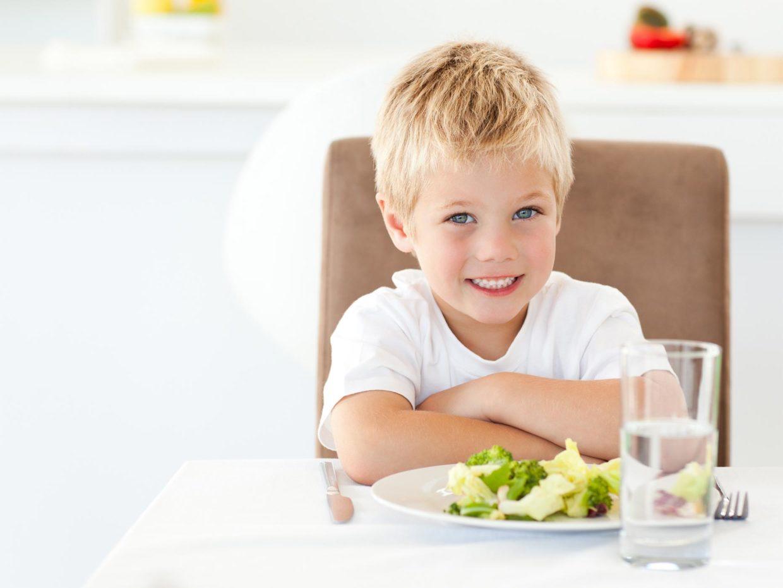 bambino biondo davanti un piatto con cibo sano