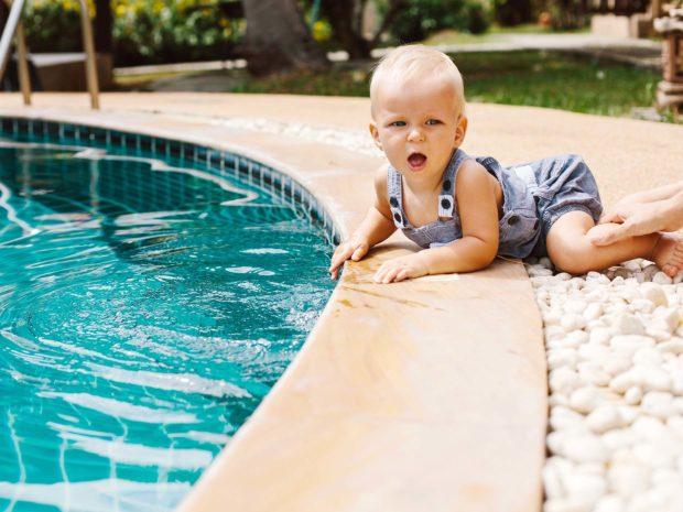 piccolo bambino gattona vicino al bordo di una piscina