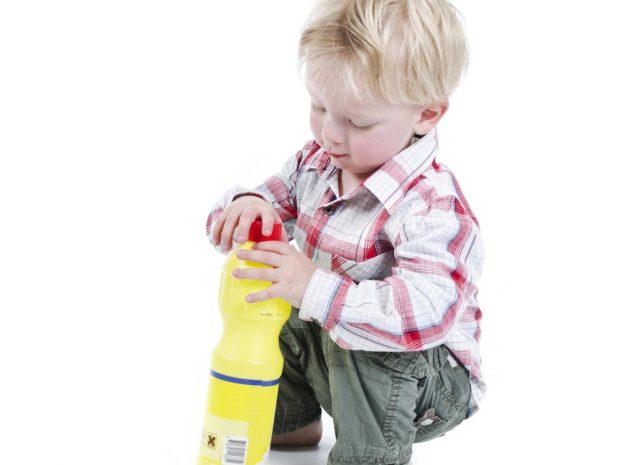 bambino gioca con una bottiglia di liquido velenoso