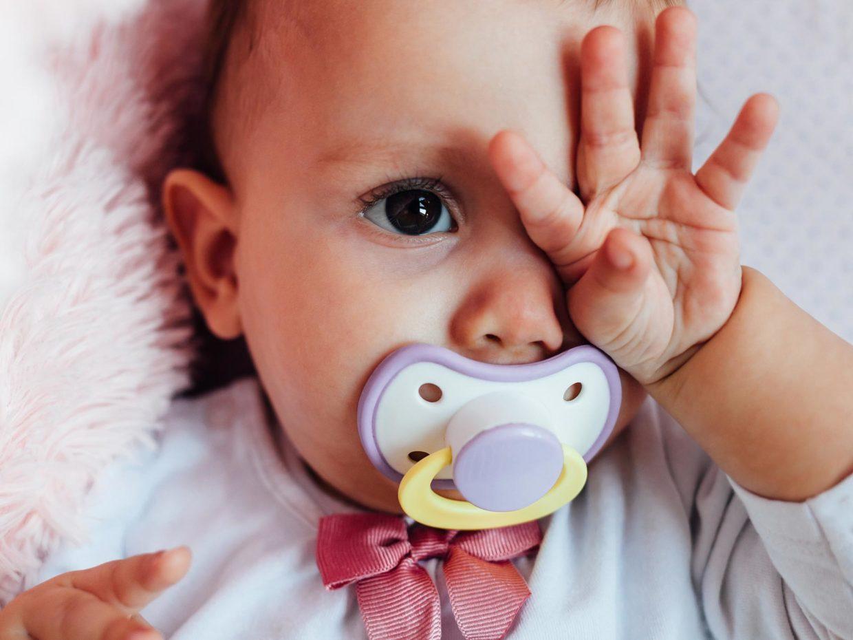 neonato con ciuccio si tocca con la mano l'occhio