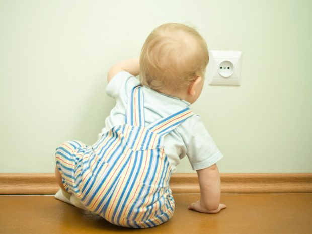 bambino si avvicina curioso alla presa della corrente elettrica