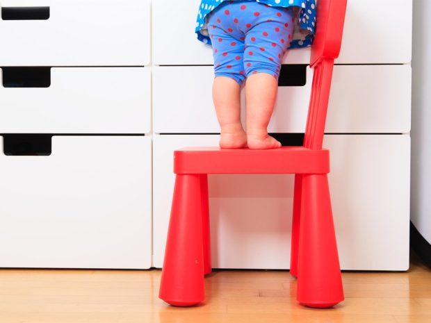 bambina piccola in piedi su una sedia di plastica rossa
