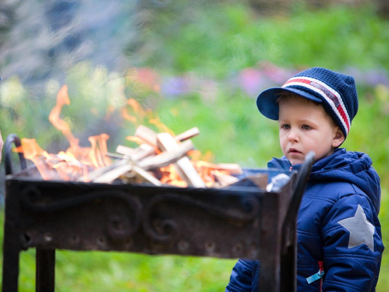 bambino con cappello osserva il fuoco della griglia