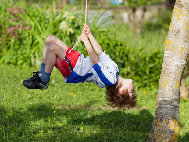 bambino gioca in maniera pericolosa sull'altalena in giardino