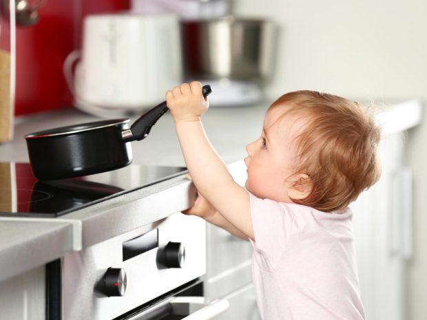 bambino prova a sollevare il pentolino dal piano cottura
