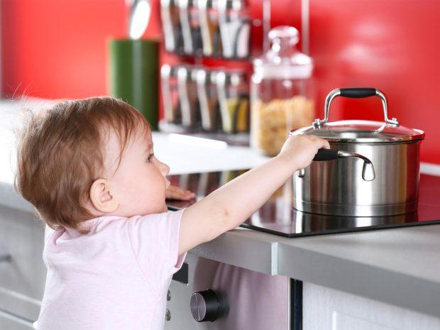 bambino prova a prendere il pentolino dal piano cottura