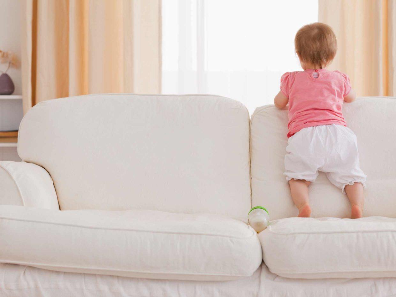 bambina piccola in piedi sopra il divano
