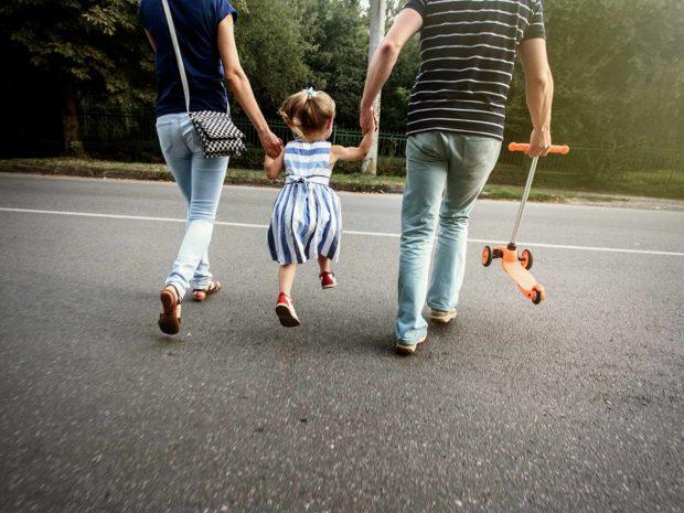 genitori danno la mano alla figlia per attraversare la strada