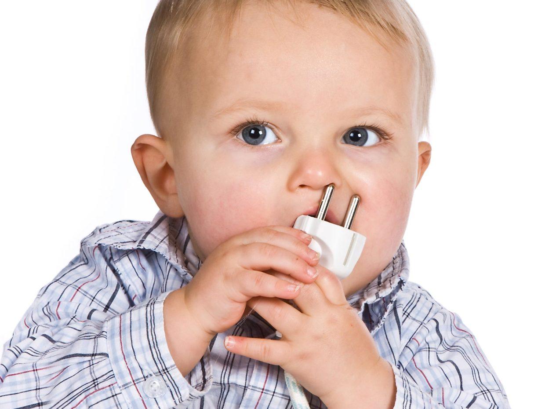 bambino con in bocca una presa elettrica