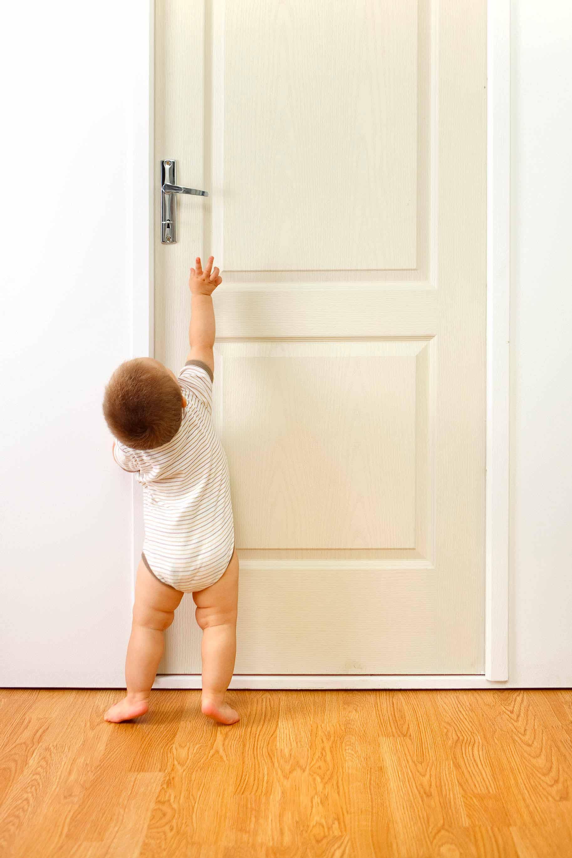 bambino prova ad aprire una porta
