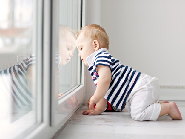 bambino gattona guardando fuori dalla porta a vetri